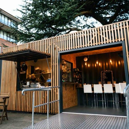 Shipping container cafe conversion with fold down deck